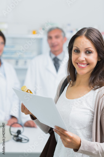 Customer holding a paper and pills while standing in a pharmacy and smiling