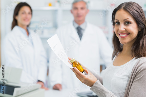 Client holding a paper and pills while standing in a pharmacy