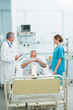 Female nurse and doctor talking in the room of a patient