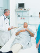 Doctor and nurse talking with a patient in a bed ward
