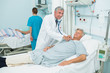 Smiling male doctor auscultating a male patient in a bed ward