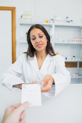 Smiling female pharmacist receiving a prescription from a customer