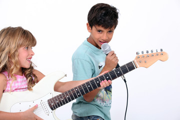 Two children singing and playing guitar