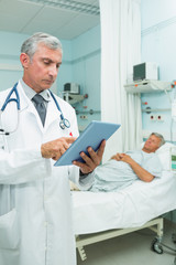 Doctor using a tactile tablet while standing