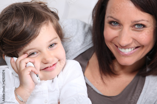 Mother and young daughter making a phone call