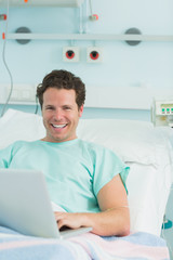 Male patient typing on a laptop while lying on a bed and laughing