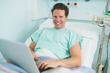Patient typing on a laptop while lying on a bed and laughing