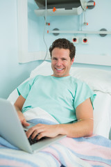 Patient using a laptop while lying on a bed and laughing
