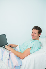 Male patient using a laptop while laying on a bed