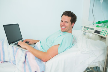 Patient using a laptop while lying on a bed