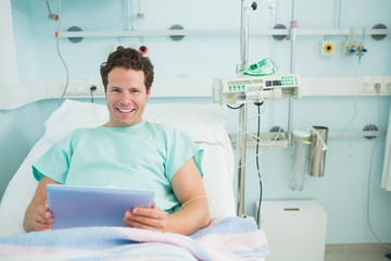 Male patient holding a tactile tablet while lying on a bed