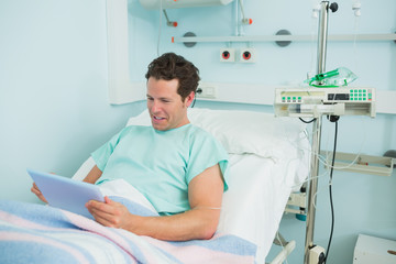 Happy patient holding a tactile tablet while lying on a bed