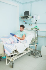 Focus male patient holding a tactile tablet while lying on a bed