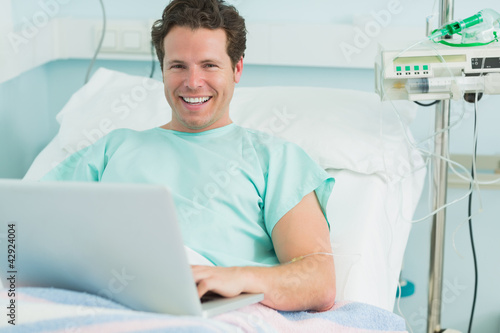 Smiling male patient typing on a laptop while lying on a bed
