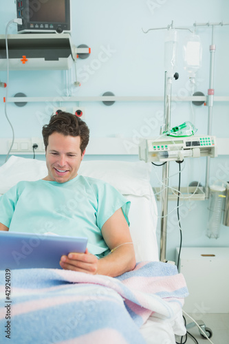 Smiling male patient using a tactile tablet while lying on a bed