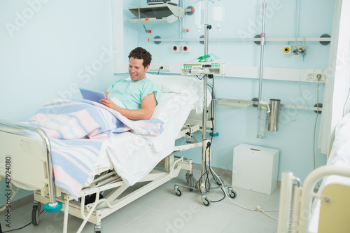 Smiling male patient holding a tactile tablet while lying on a bed