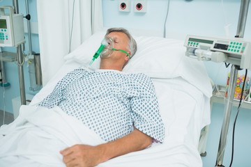 Unconscious patient on a bed with an oxygen mask