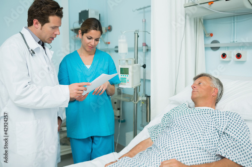Doctor and nurse looking at a paper with a patient