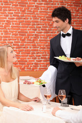 Waiter serving food to customer