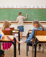 Schoolgirl giving schoolfellow a letter