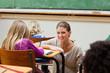 Helpful teacher next to students desk