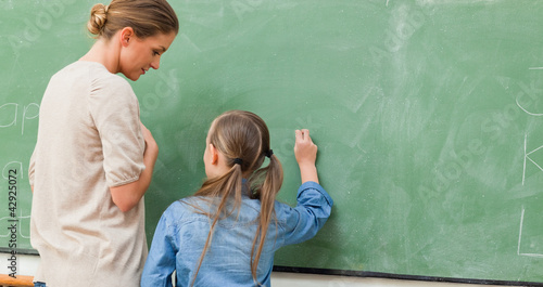 Teacher and pupil next to blackboard