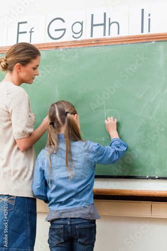 Teacher and student writing on blackboard together