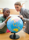 Teacher explaining globe to a student