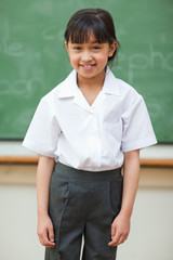 Smiling schoolgirl in front of blackboard
