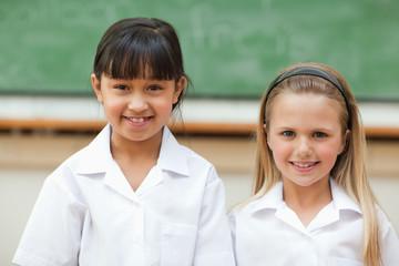 Smiling girls in front of blackboard