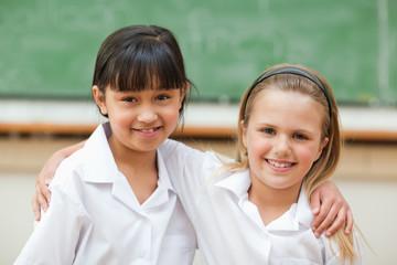Happy girls in school uniform in front of blackboard