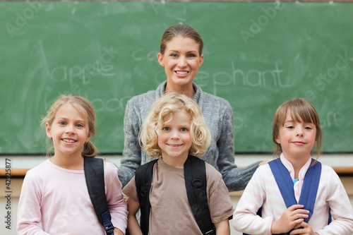 Teacher with her students standing in front of black board