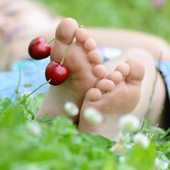 Kinderfüße im Gras mit Kirschen