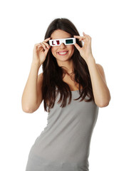 Young happy woman is watching through 3D glasses