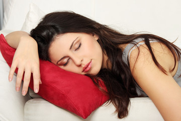 Beautiful woman is sleeping on red pillow.