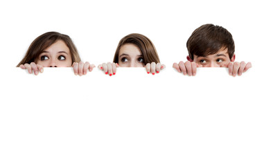 Three teenagers peeking over a white background