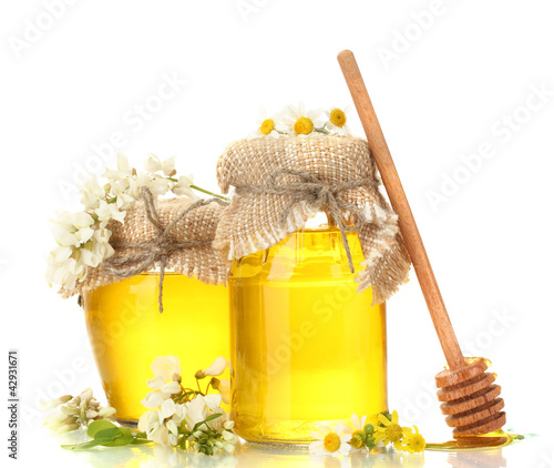 Sweet honey in jars and acacia flowers isolated on white
