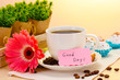 cup of coffee and gerbera beans, cinnamon sticks on wooden