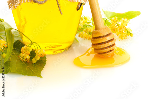 jar with linden honey and flowers isolated on white