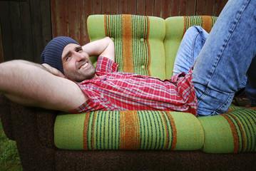 Lächelnder Mann liegt auf einer Couch