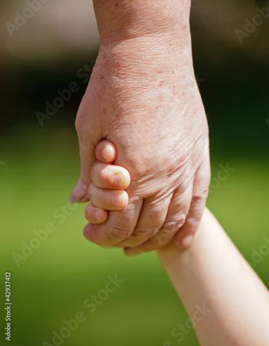 Grandma holding grandchilds hand