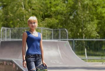 Punk girl skater with board in skatepark