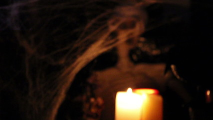 Skeleton prop with candle in front come into focus.