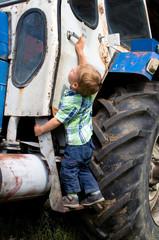 Kleiner Junge klettert auf Traktor