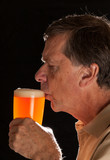 Senior man sipping from pint glass beer