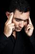 Hispanic man suffering a strong headache isolated on black