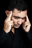 Hispanic man suffering a strong headache isolated on black