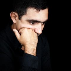 Hispanic man thinking with a fist on his chin isolated on black
