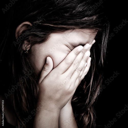 Grunge portrait of a girl crying on a black background