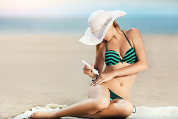 Portrait of woman taking skincare with sunscreen lotion at beach